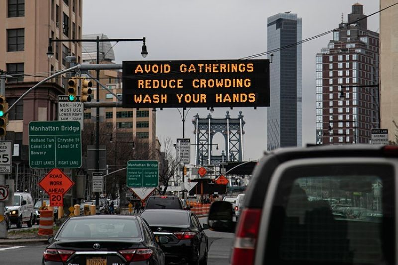 USA. In this March 19, 2020, file photo, the Manhattan bridge is seen in the background of a flashing sign urging commuters to avoid gatherings, reduce crowding and to wash hands in the Brooklyn borough of New York. (AP)