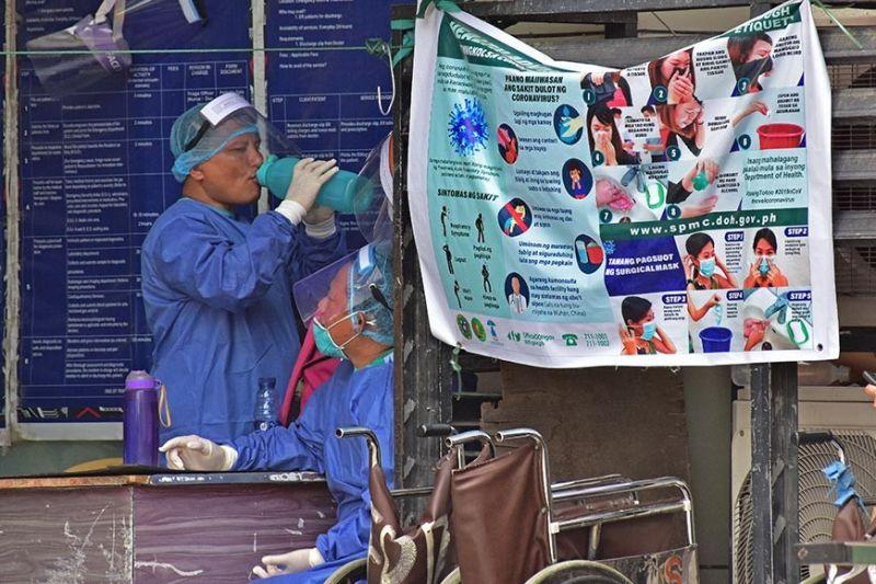 DAVAO. Gitungab sa usa ka health worker sa Southern Philippines Medical Center (SPMC) sa Davao City ang iyang butanganan og tubig atol sa ilang pagpahulay kilid sa pultahan sa emergency room kung asa tanang mga doktor, nars, ug staff sa mga ospital, okupado sa pagpangandam sa mga posibleng mataptan og Covid-19 sa Davao City. (Macky Lim)