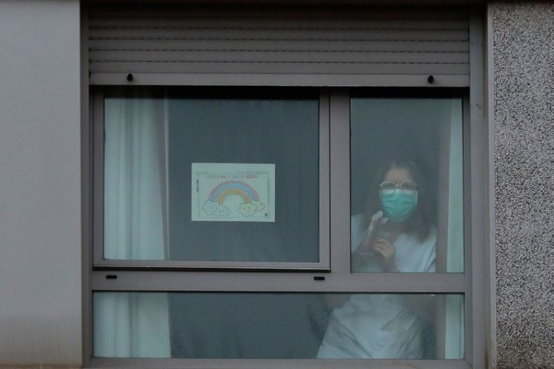 SPAIN. A nurse looks out from a window next to a banner reading in Spanish