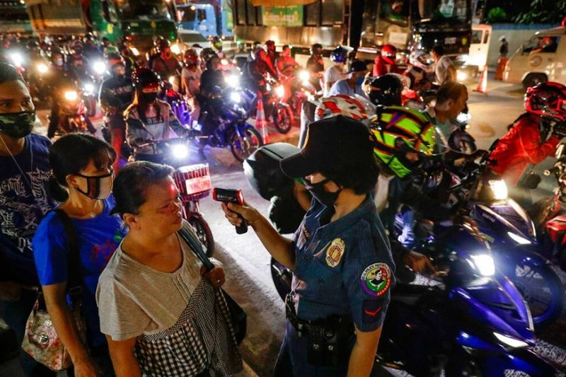 A police officer reads the temperatures of people at a checkpoint as part of precautionary measures against the spread of the new coronavirus in Manila, on Monday, March 16, 2020. For most people, the new coronavirus causes only mild or moderate symptoms. For some, it can cause more severe illness, especially in older adults and people with existing health problems. (AP)