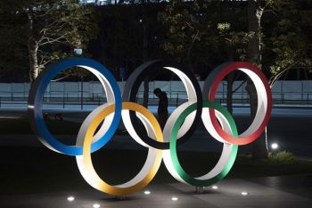 A man is seen through the Olympic rings in front of the New National Stadium in Tokyo, Tuesday, March 24, 2020. IOC President Thomas Bach has agreed