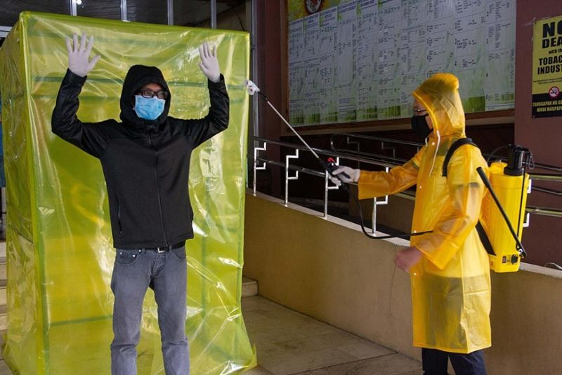 BAGUIO. A sanitation engineer tests the newly setup sanitation tent at the Baguio Health Department Tuesday morning. The tent is used to disinfect persons coming inside the building especially the health workers, frontliners and employees who cannot afford to stay at home amid the pandemic. The city government began setting up sanitation tents with spray system in critical public areas on Monday, March 23, 2020. (Photo by Jean Nicole Cortes)
