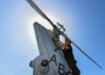 """ARABIAN SEA. Aviation Machinist Mate 3rd Class Keith Gonzales, from Iloilo, Philippines, attaches tail gear box cowling to an MH-60R Sea Hawk helicopter, assigned to the """"Proud Warriors"""" of Helicopter Maritime Strike Squadron (HSM) 72, on the flight deck of the guided-missile cruiser USS Normandy (CG 60). (US Navy photo by Mass Communication Specialist 2nd Class Michael H. Lehman)"""