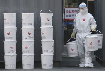 SOUTH KOREA. A staff member carries plastic buckets containing medical waste from new coronavirus patients at the Dongsan Hospital in Daegu, South Korea, Wednesday, March 25, 2020. (AP)