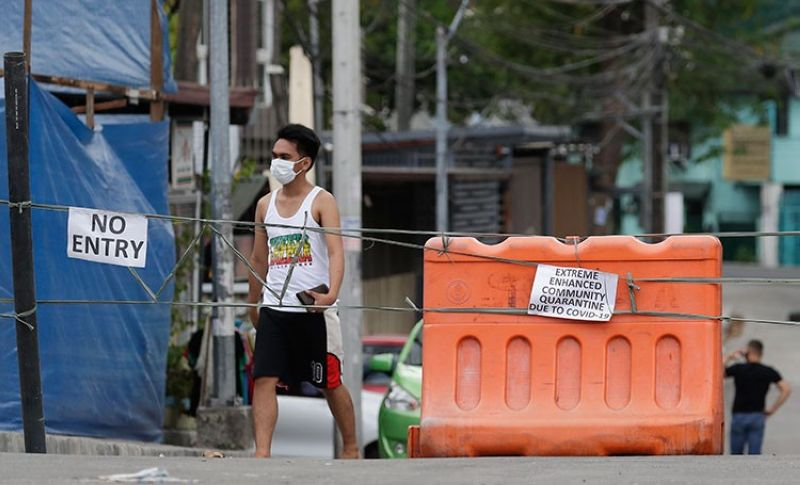 MANILA. A man wearing a protective mask walks past an area cordoned off for an enhanced community quarantine aimed to prevent the spread of the new coronavirus in Manila, Philippines, Tuesday, March 24, 2020. (AP)