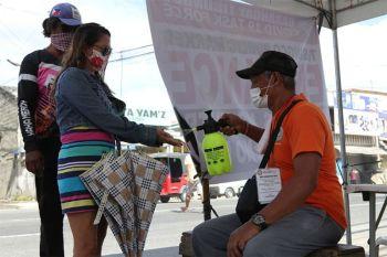 DAVAO. Gi-sprayhan og alcohol sa usa ka personahe sa Barangay Tibungco ang kamot sa babaye una makasulod sa palengke sa maong barangay aron maseguro ang ilang seguridad batok Covid-19. (Hulagway ni Mark Perandos)