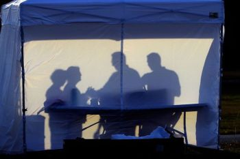 USA. In this Wednesday, March 25, 2020 file photo, medical personnel are silhouetted against the back of a tent before the start of coronavirus testing in the parking lot outside of Raymond James Stadium in Tampa, Florida. (AP)