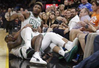 Si Marcus Smart (ibabaw) ug iyang kauban sa Boston Celtics nga nangatumba niining aktoha haduol sa mga fans atol sa usa nila ka duwa batok sa Cleveland Cavaliers sa NBA. AP File