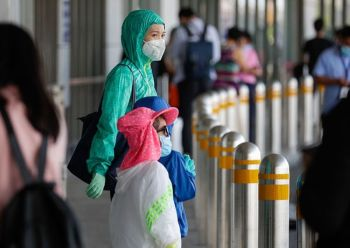 MANILA. Foreigners wear face masks and jackets outside the departure area of Manila's International Airport, Philippines on Wednesday, March 18, 2020. (AP)