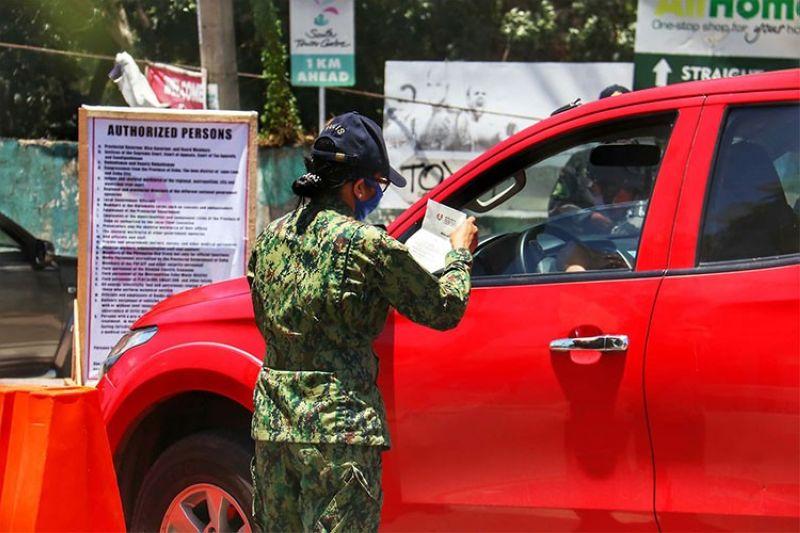CEBU. Gisusi sa myembro sa security group ang papeles sa usa ka pribadong sakyanan atol sa pagpatuman sa border control sa tibuok probinsya sa Sugbo. (Amper Campana)