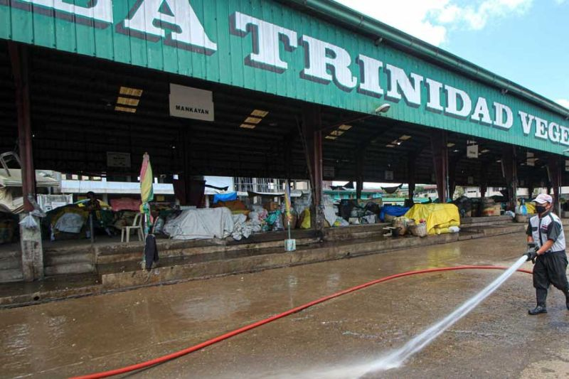 CLEAN-UP. A worker helps disinfect the La Trinidad Vegetable Trading Post on Monday, March 30, 2020 after operations were suspended by Mayor Romeo Salda. (Photo by Jean Nicole Cortes)