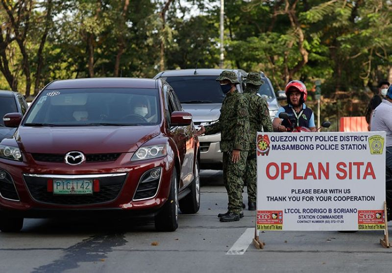 MANILA. Police stop motorists at a checkpoint in Metro Manila, Philippines on Wednesday, March 18, 2020. (AP)