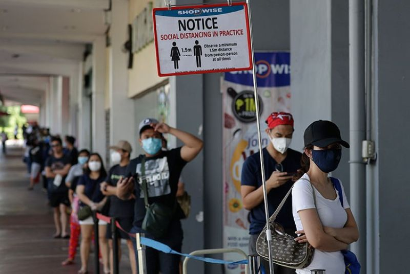 MANILA. A reminder stands beside a long line of people wearing protective masks outside a supermarket during a community quarantine to help curb the spread of the new coronavirus in Manila, Philippines on Wednesday, April 1, 2020. (AP)