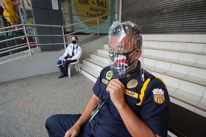 BENGUET. A security guard of a mall in La Trinidad uses DIY face protector made from magnetic plastic cover which is more comfortable than the company provided protective gear. (Photo by Jean Nicole Cortes)