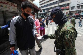 PAMPANGA. Personnel deployed at the Baguio City market is doubled after Saturday's market nightmare. Police check the quarantine pass before entry to the market and make sure social distancing is observed. Photo by Jean Nicole Cortes