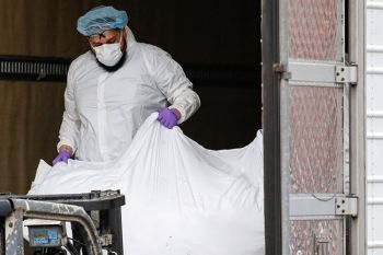 USA. A body wrapped in plastic is loaded onto a refrigerated container truck used as a temporary morgue by medical workers wearing personal protective equipment due to Covid-19 concerns, Tuesday, March 31, 2020, at Brooklyn Hospital Center in the Brooklyn borough of New York. (AP)