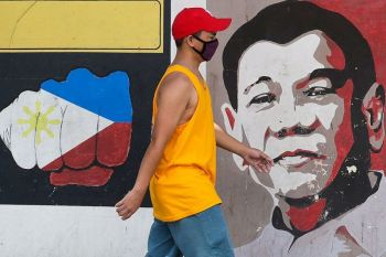 MANILA. A man wearing a protective mask walks past an image of Philippine President Rodrigo Duterte in Manila, Philippines on Friday March 20, 2020. (AP)
