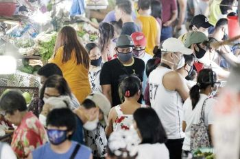 FIRST THINGS FIRST. Men wearing protective masks buy food before the Munoz market closes in Metro Manila, Philippines. Retail player Robert Go says the shopping behavior of Filipinos is focused on basic goods nowadays as the coronavirus outbreak has taken a toll on the financial health of most consumers. (AP Photo)