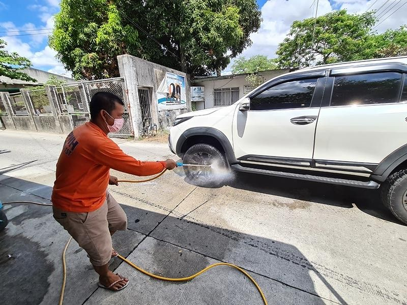 PAMPANGA. A maintenance crew of the DPWH-Pampanga 1st District Engineering Office sprays disinfectant on the wheels of an SUV before entering the DPWH-3 compound in Barangay Sindalan, City of San Fernando, Pampanga. The DPWH-Central Luzon and its district offices are in the forefront of fighting the Covid-19 pandemic. (Chris Navarro)