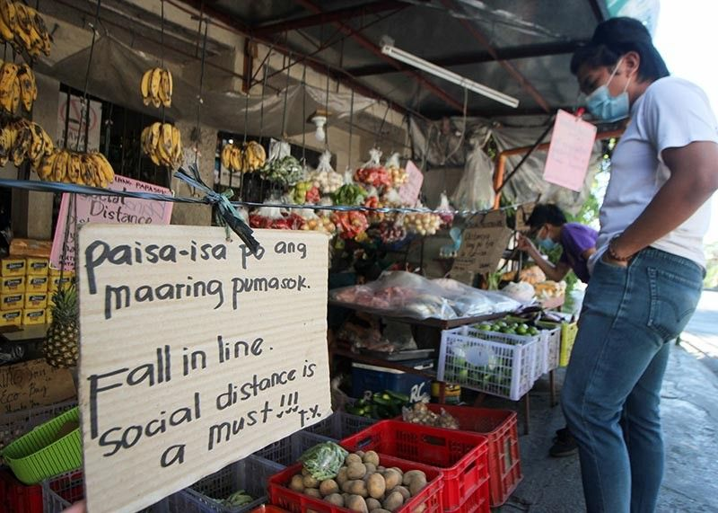 BAGUIO. Customers follow social distancing at a store in Campo Sioco, Baguio City. Several signs and a barrier are placed as a safety precaution against Covid-19. (Photo by Jean Nicole Cortes)