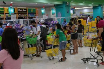 DAVAO. Midagsa ang mga tawo sa usa ka dakong mall sa Tibungco, siyudad sa Davao niadtong Sabado, April 4, 2020, pipila ka oras una ang pag-implementa sa enhanced community quarantine sa siyudad aron mamalit sa ilang panginahanglan. (Hulagway ni Mark Perandos)