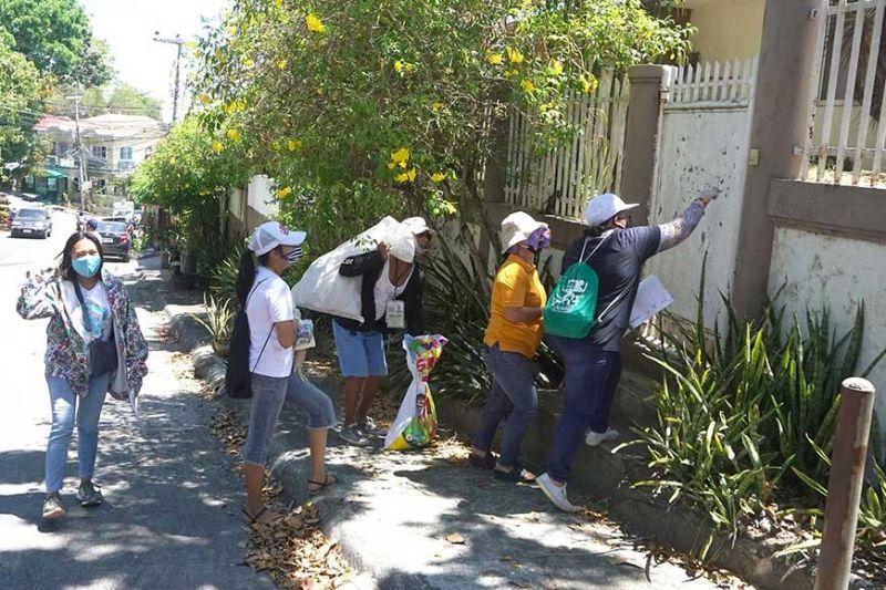 NANGHATAG: Mga barangay worker sa Brgy. Lawaan 1, Talisay City nanungko sa mga balay sa Camella Homes Subdivision aron pagpanghatag sa relief goods gikan sa Talisay City Hall taliwa sa gipatuman nga enhanced community quarantine (ECQ). (Alex Badayos)