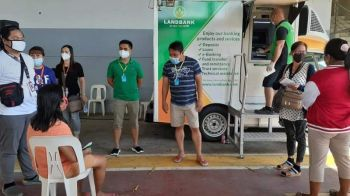 PAMPANGA. Candaba Mayor Rene Maglanque talks to a resident who is among the first to try the Landbank of the Philippines' mobile ATM. Beside him is Vice Mayor Michael Sagum. (Contributed photo)