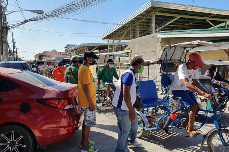 PAMPANGA. A pedicab driver in Masantol pedals back home after receiving relief goods from the municipal government. (Contributed photo)
