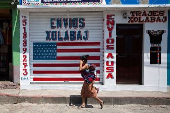 GUATEMALA. In this April 3, 2020 photo, a woman carrying a child walks past a closed courier business featuring a US flag and the Spanish phrase: