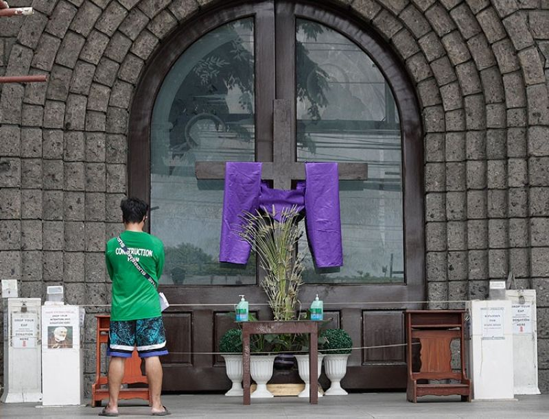 MANILA. A man prays outside a closed St. Peter's Parish on Maundy Thursday, April 9, 2020, in Manila, Philippines. In the Philippines, Asia's bastion of Catholicism, masses and other solemn gatherings in packed churches and bizarre folk ritual like real-life crucifixions that draw thousands of tourists and penitents each year in a rice field north of Manila, have been put off due to a lockdown to prevent the spread of the new coronavirus on the main northern region of Luzon, home to more than 50 million largely Catholic Filipinos. (AP)