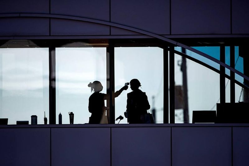 MINNESOTA. Amid coronavirus concerns, a healthcare worker takes the temperature of a visitor to Essentia Health who was crossing over a skywalk bridge from the adjoining parking deck, Friday, April 10, 2020, in Duluth, Minnesota. (AP)