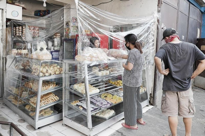 BUSINESS AS USUAL. A bakery uses plastic sheets as protection during an enhanced community quarantine to help curb the spread of the new coronavirus at the usually busy downtown in Manila, Philippines. (AP photo)