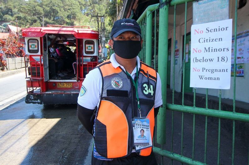 CARRYING ORDERS. A Public Order and Safety Officer at Barangay San Luis makes sure that no senior citizens, minors and pregnant women are going out of their barangay during the ECQ. Photo by Jean Nicole Cortes