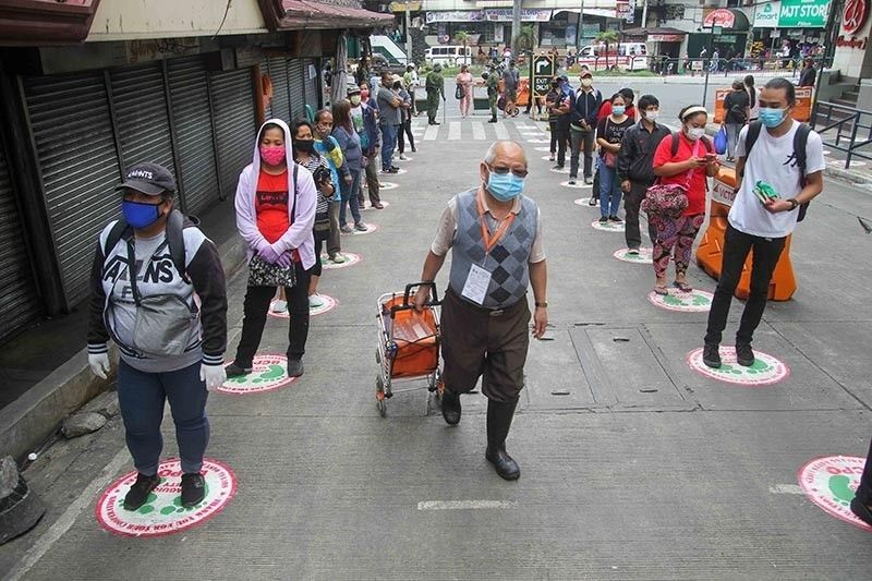 BAGUIO. Market goers follow the newly painted guides made by the Baguio City Police Office in an effort to promote social distancing inside the Baguio public market. (Jean Nicole Cortes)