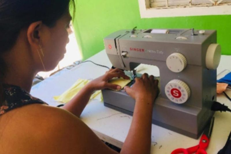 BACOLOD. Jeramie Abadies-Eslais, president of the Parent-Teacher Association of Talave Elementary School, works on an improvised face mask using one of the sewing machines donated by San Carlos Sun Inc. (Contributed photo)
