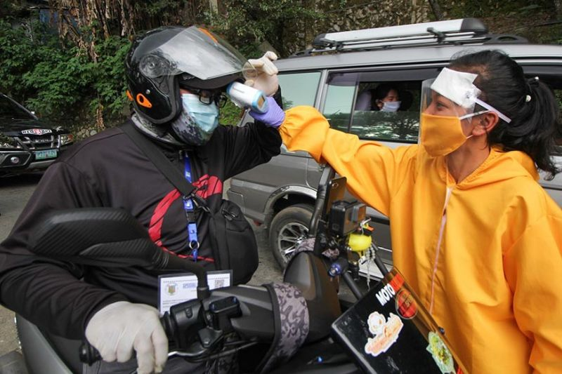 BAGUIO. A resident of Itogon checks the temperature of motorists in the area. Although Itogon is still Covid-19 free as of Saturday, May 23, 2020, the town is following strict health protocols against the dreaded coronavirus disease. (Photo by Jean Nicole Cortes)