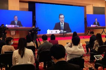 CHINA. In this Sunday, May 24, 2020, file photo, China's Foreign Minister Wang Yi is seen broadcasted remotely on big screens at the media center during a press conference held on the sideline of the National People's Congress in Beijing. (AP)