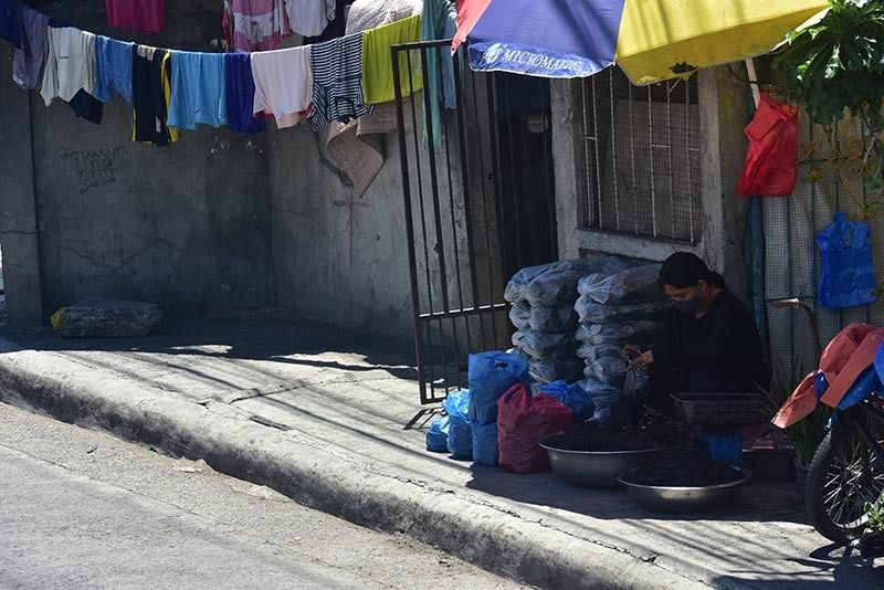 DAVAO. Despite the indefinite closure of Agdao Public Market in Davao City, a vendor continues to repack charcoal near Agdao Flyover to  continue selling despite the market's closure due to rapid tests. (Macky Lim)