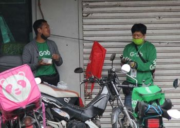 BAGUIO. Food delivery guys take a quick break for lunch as they wait for orders to be delivered to households during quarantine. The demand for food delivery sky rocketed during the quarantine period, however, some reports on social media show buyers pranking food delivery guys or abruptly cancelling orders. (Photo by Jean Nicole Cortes)