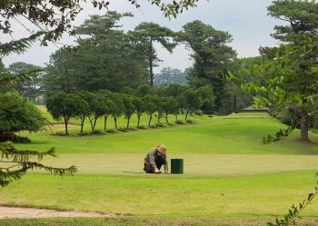 BAGUIO. In anticipation of golfers returning to the fairways this week, a worker from Baguio Country Club maintains the greens of the golf course. (Photo by Jean Nicole Cortes)