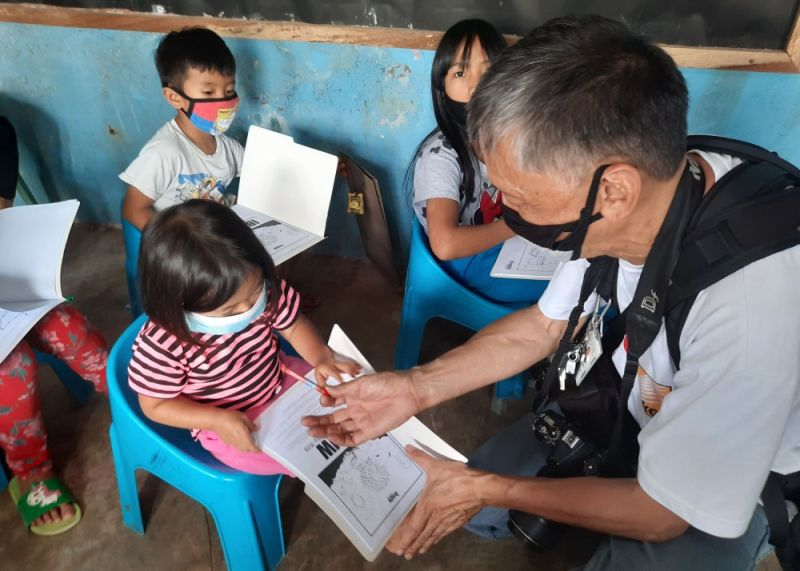 BENGUET. Photographer Ompong Tan assists a young girl in Samoyao, Ampucao, Itogon. A group of artists in Baguio City recently donated coloring book kits to different communities in Baguio City and Benguet in a bid to cushion restrictions of the community quarantines felt by children. (Karlo Marko Altomonte)