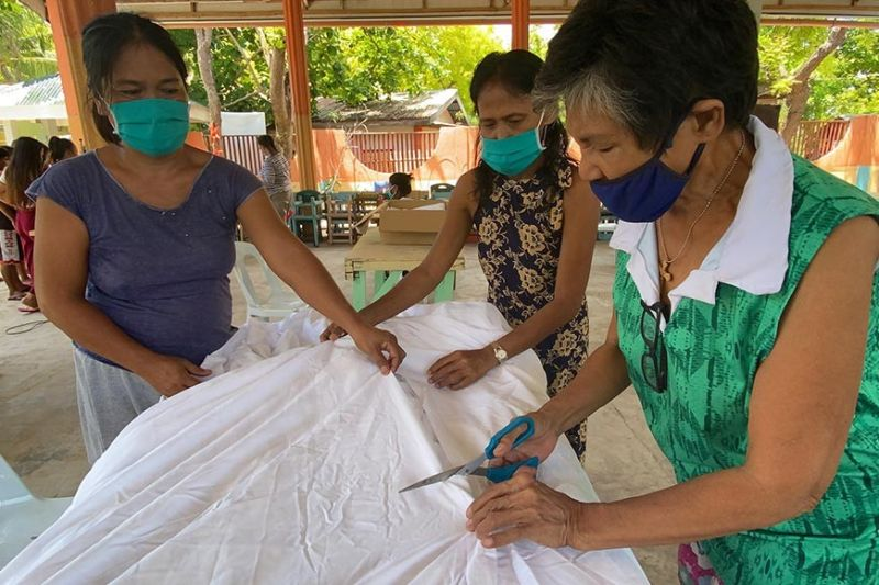 MAKING MASKS. Volunteer residents of Gilutongan Island off Cordova town sew masks from used, clean bed sheets collected by the Shangri-La Group. (Contributed photo)