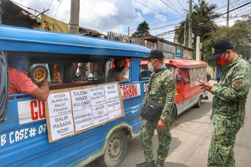 CEBU. Cebu City policemen call the attention of a jeepney driver who has placed a placard expressing the lament of public utility drivers who have lost their income because of the prolonged lockdown and consequently the prohibition of public transport. The policemen asked the driver to remove the placards on Monday, July 20, 2020. (Amper Campana)