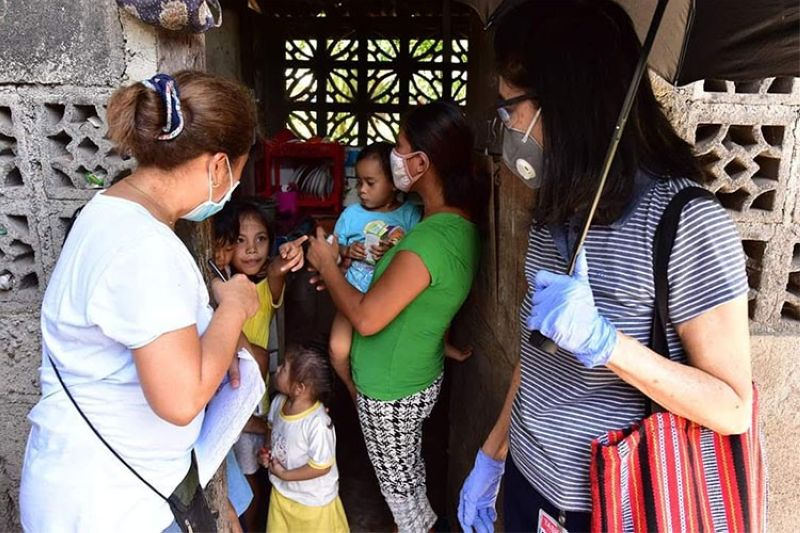DUMAGUETE. Dumaguete City Health Officer Dr. Ma. Sarah Talla (right) leads the team in their house-to-house dengue campaign in Barangay Banilad. (PIA)