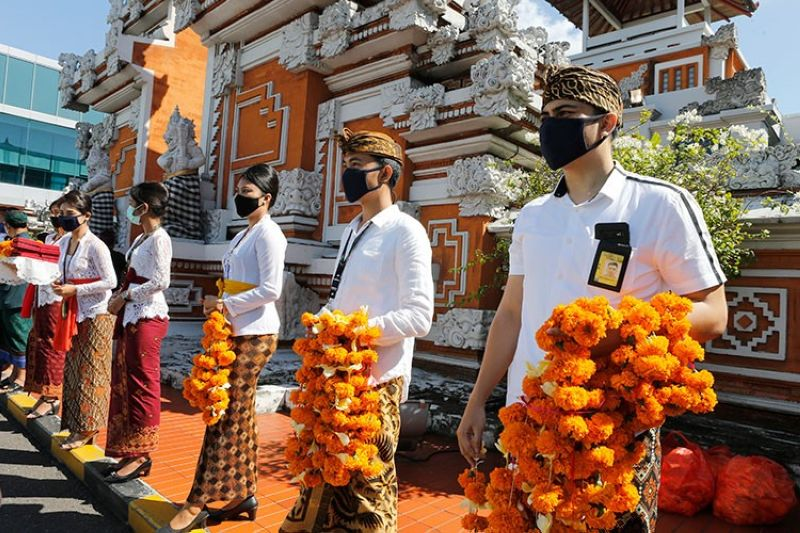 INDONESIA. Airport officers wearing face masks line up as they hold flowers to welcome passengers at Bali airport, Indonesia on Friday, July 31, 2020. Indonesia's resort island of Bali reopened for domestic  tourists after months of lockdown due to a new coronavirus. (AP)