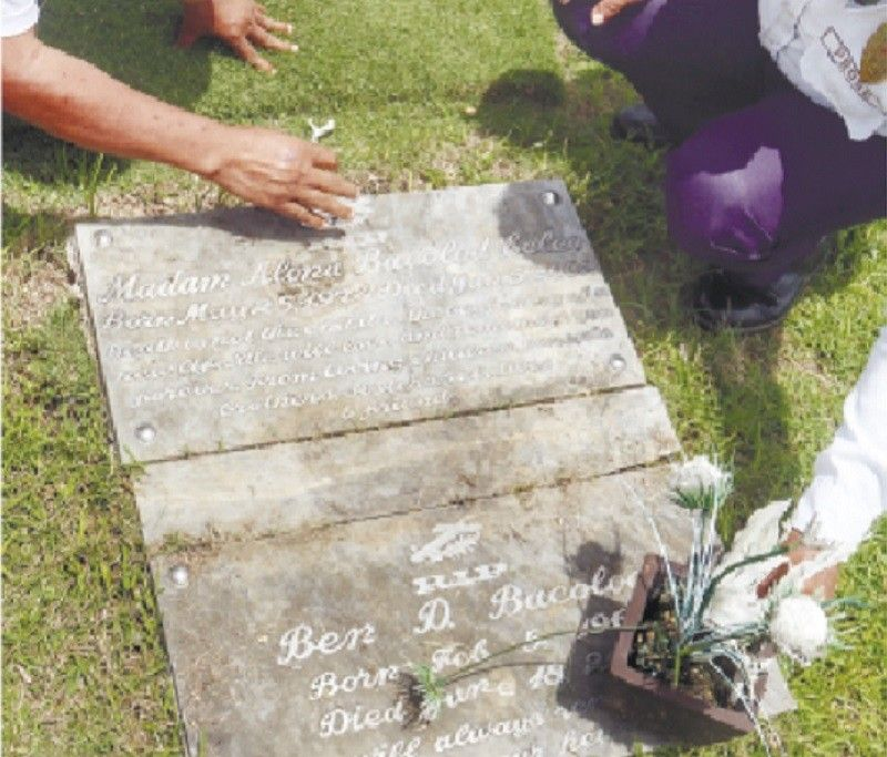 VICTIMS' GRAVES. A guard of Cebu South Memorial Garden in Barangay Mohon, Talisay City and his friend clean the grave stones of Alona Bacolod-Ecleo, her parents and siblings on Friday, July 31, 2020. Alona's husband, Philippine Benevolent Missionaries Association (PBMA) supreme master Ruben Ecleo Jr., was convicted in 2012 for killing her in 2002. Alona's parents and two siblings were also gunned down in their residence in Mandaue City by a PBMA member in 2002. / AMPER CAMPAÑA