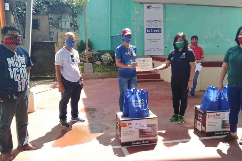 Cherryl Navarro, one of the beneficiaries of the Livelihood Seeding Program-Negosyo Serbisyo sa Barangay, receives an electric oven and other tools from the Department of Trade and Industry to be used for her pizza and waffle business. (Contributed photo)