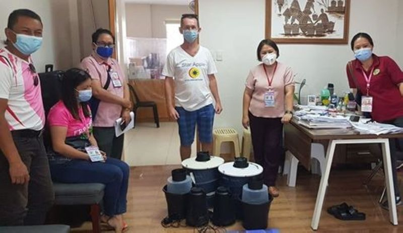 SOUTHERN LEYTE. Pascal Canning (center, standing) of Star Apple Foundation delivers mosquito traps to the barangays in Maasin City, Southern Leyte to protect the residents from dengue. The mosquito traps were donated by Biogents AG from Germany. (Photo courtesy of Star Apple Foundation)