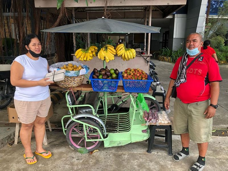 FOR THE FAMILY. Raquel Sucon (left) and Earl Lopez, security guards at Ateneo de Davao University, have started selling fruits in front of the school to provide for their respective families. (Nino Velasco, Addu intern)