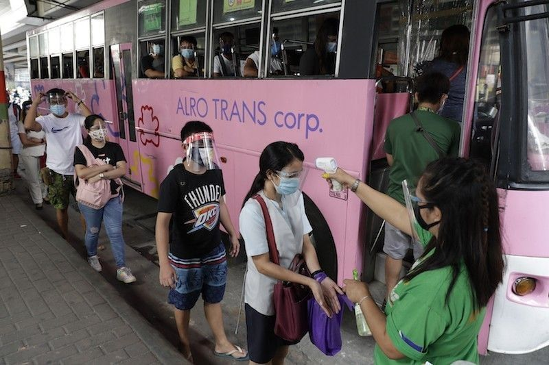 MANILA. A woman checks the temperature of passengers to help curb the spread of Covid-19 at a bus stop in Quezon City, Philippines on August 19, 2020. (AP)